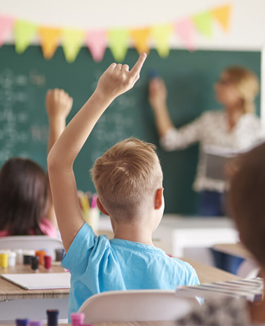 Boy with hand raised in classroom